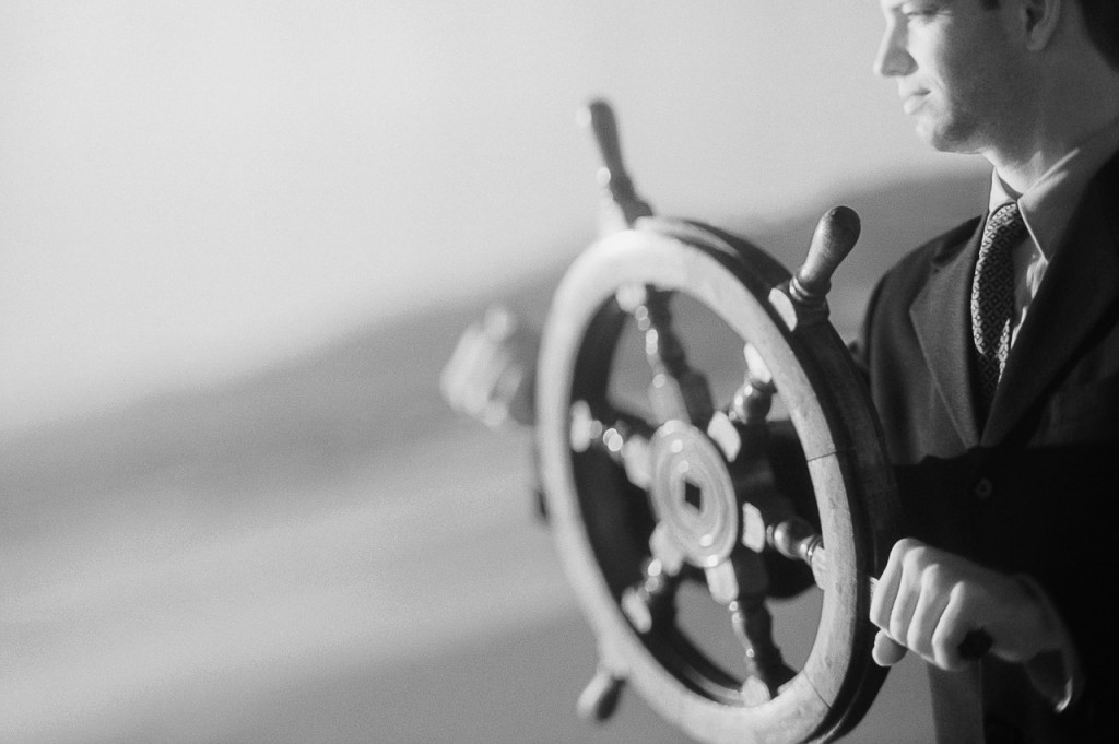 Businessman Turning Ship Wheel